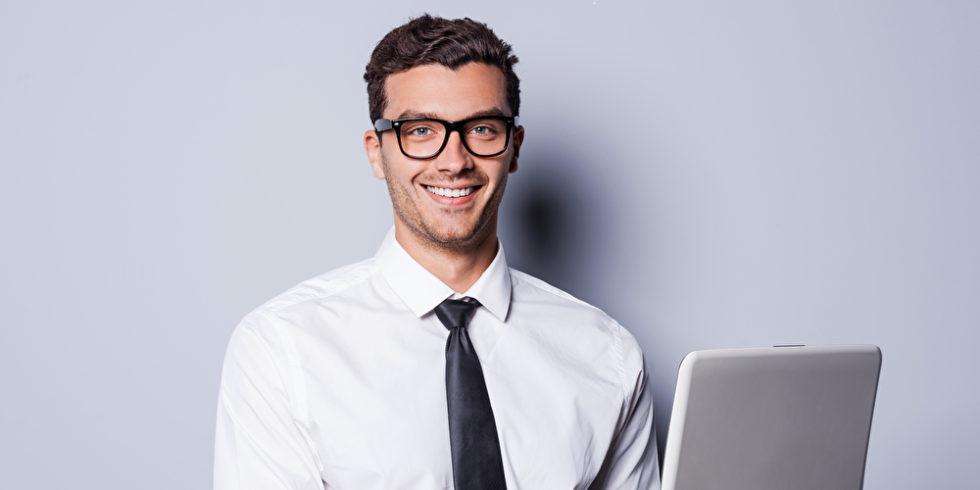 Mann im Hemd und Krawatte am Laptop arbeiten und lächelnd stehen vor grauem Hintergrund