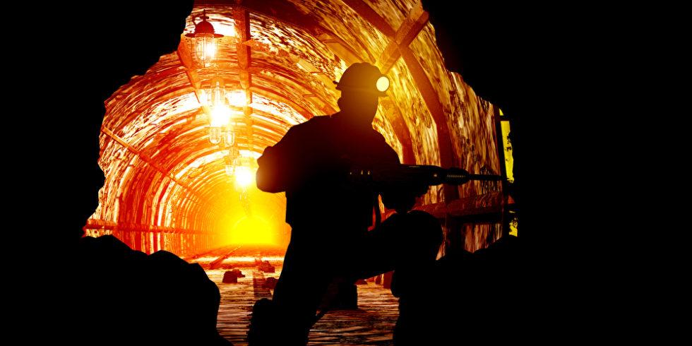 Silhouette eines Mannes vor rot glühender Mine