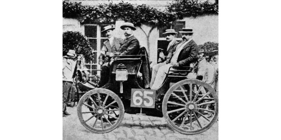 Schwarz-weiß Bild eines Wagens mit der Nummer 65 auf Kopfsteinpflaster. Vier Herren sitzen darin