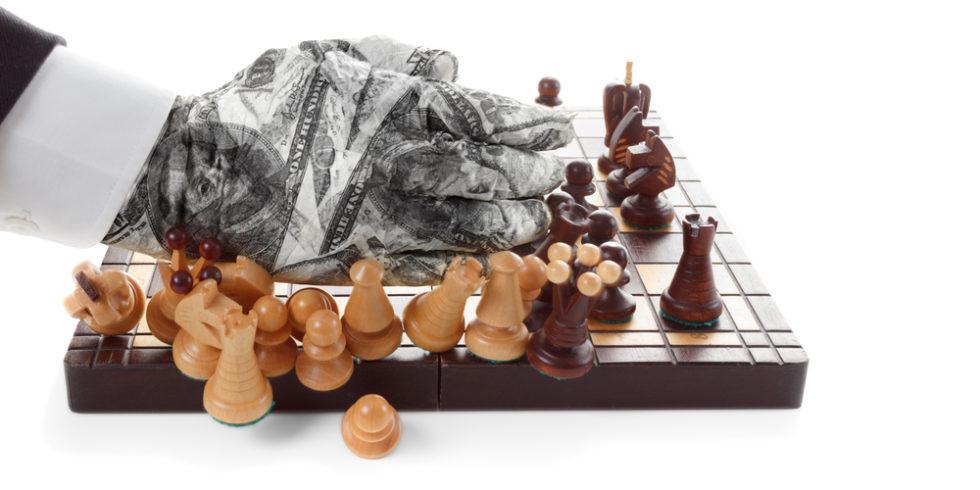 Hand fegt Schachfiguren von einem Brett