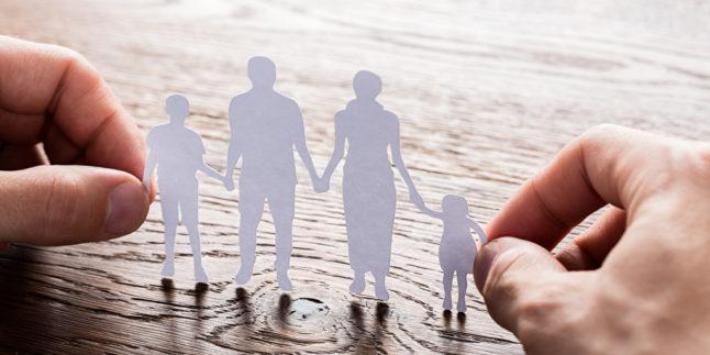 Zwei Hände halten Silhouetten auf Papier von einer Familie, zwei Kindern und zwei Erwachsenen, die sich an den Händen halten