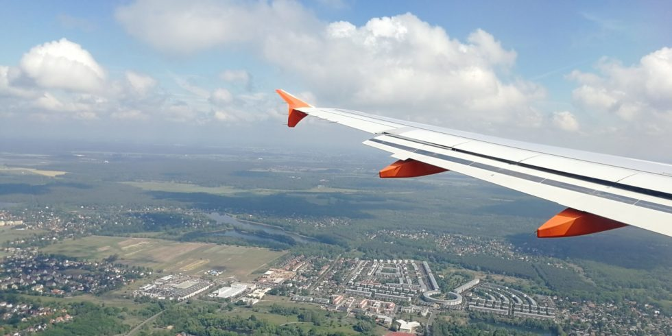 Blick aus dem Flugzeug auf die Tragfläche und eine Stadt von oben