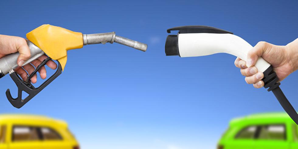 Ein Stecker und ein Zapfhahn werden über zwei Autos gehalten