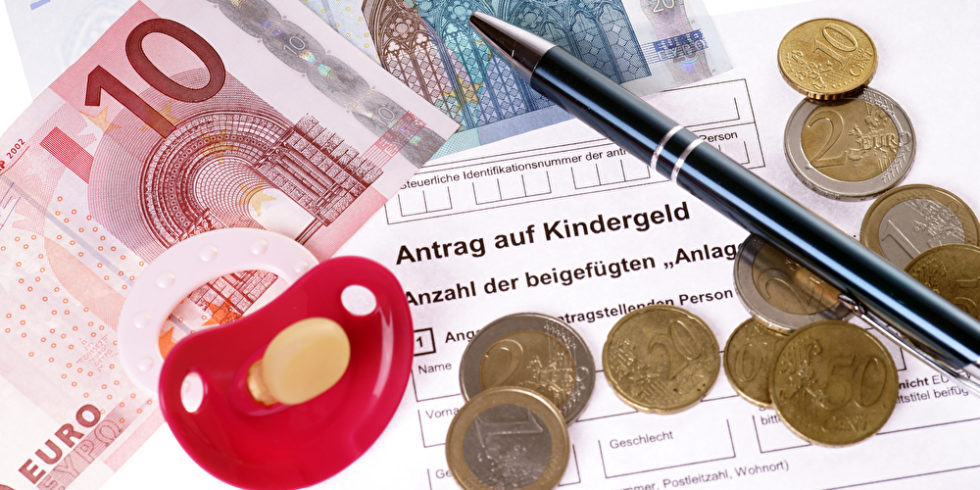 EUroscheine und Münzen sowie ein Schnuller liegen auf einem ausgedrucktem Antrag auf Kindergeld