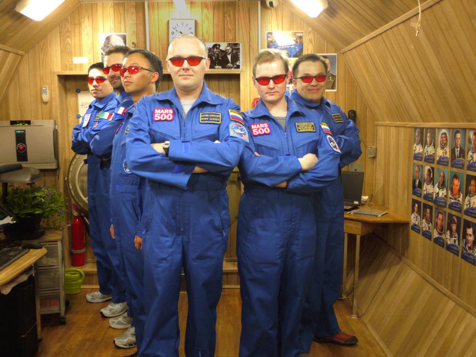Sechs Männer mit roten Brillen in hölzerner Kapsel