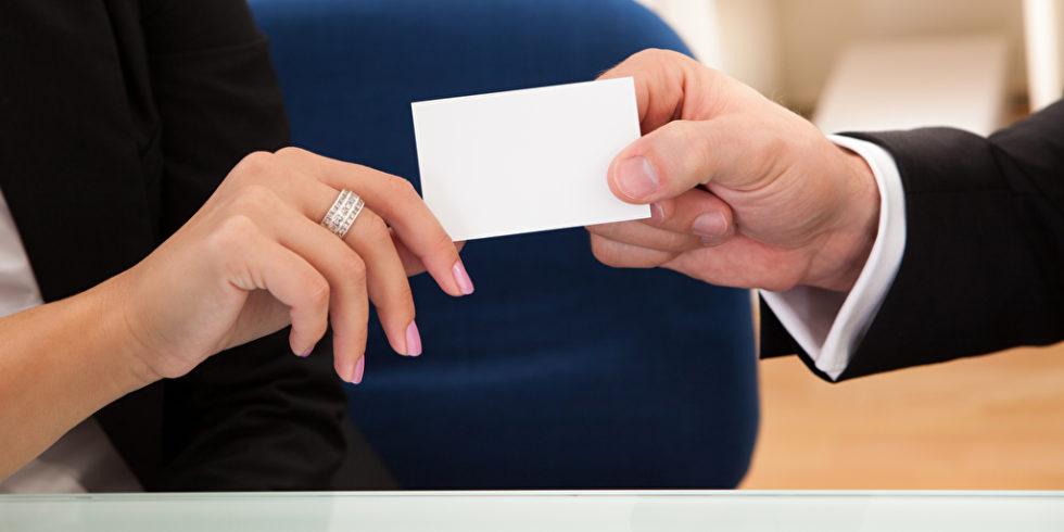 Frauen- und Männerhand bei Übergabe einer Visitenkarte