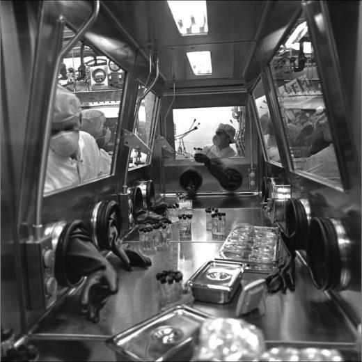schwarz-weiß Bild von Wissenschaftlern, die Proben in einem Glaskasten untersuchen
