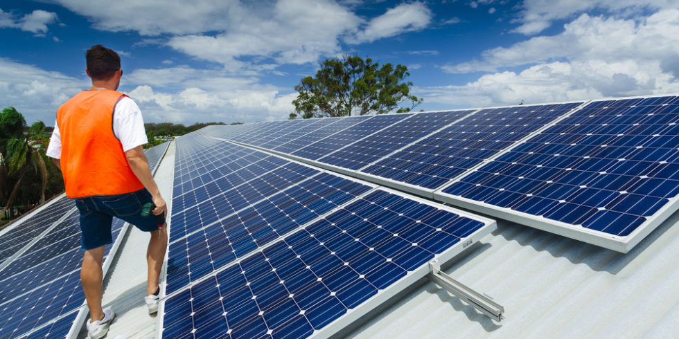 Mann mit Warnweste auf Solardach