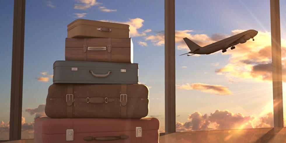 Koffer gestapelt vor einem Fenster. Dort steigt im Hintergrund ein Flugzeug hoch