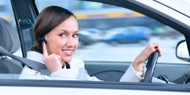 Frau mit Bluetooth Sprechanlage im Auto