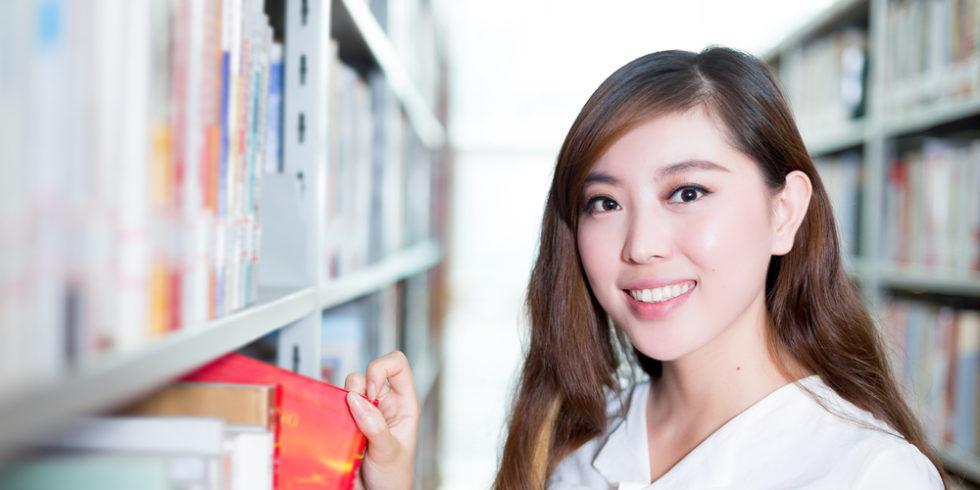 junge Frau im Gang einer Bibliothek