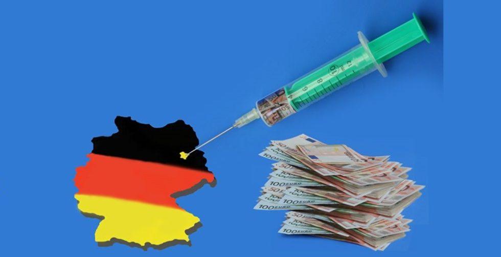 Deutschlandkarte neben einem Stapel 100-Euro-Scheine und einer Spritze, die mit Geld aufgezogen ist