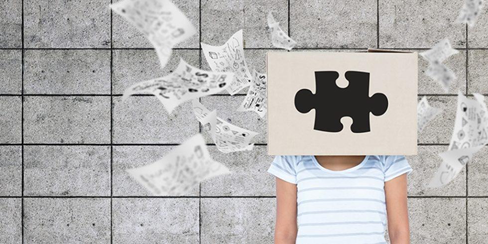 Frau mit Blatt vor dem Kopf, auf dem ein Puzzleteil abgebildet ist