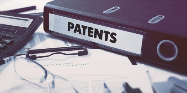 Patentordner auf Schreibtisch mit Brille und Papieren