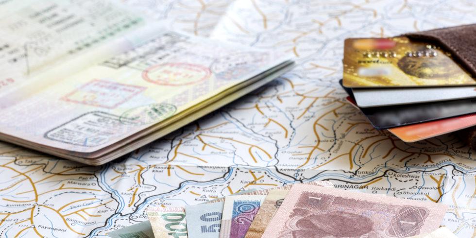 Geld, Reisepass und Kreditkarten liegen auf einer Landkarte