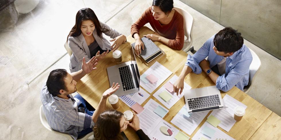 Asiatische und internationale Mitarbeiter an einem Tisch
