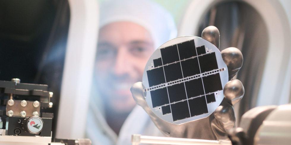 Forscher mit weißem Schutzanzug hält runde Solarzelle ins Bild