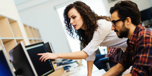 Junge Frau und junger Mann vor PC