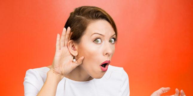Frau hält sich Hand hinter das Ohr und guckt erstaunt vor orangenem Hintergrund