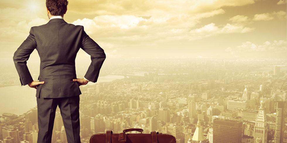 Mann mit Koffer steht auf einer Mauer vor einer goldenen Stadt