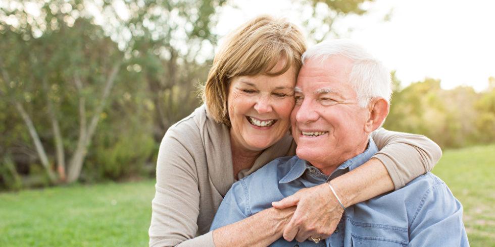 Junggebliebenes Rentnerpaar lachend im Grünen