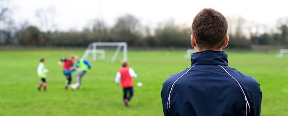 Mann schaut auf einen Fußballplatz, auf dem Kinder spielen