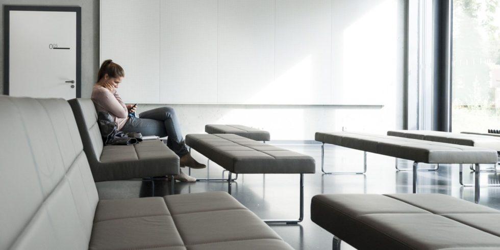 Frau sitzt alleine in einem Seminarraum