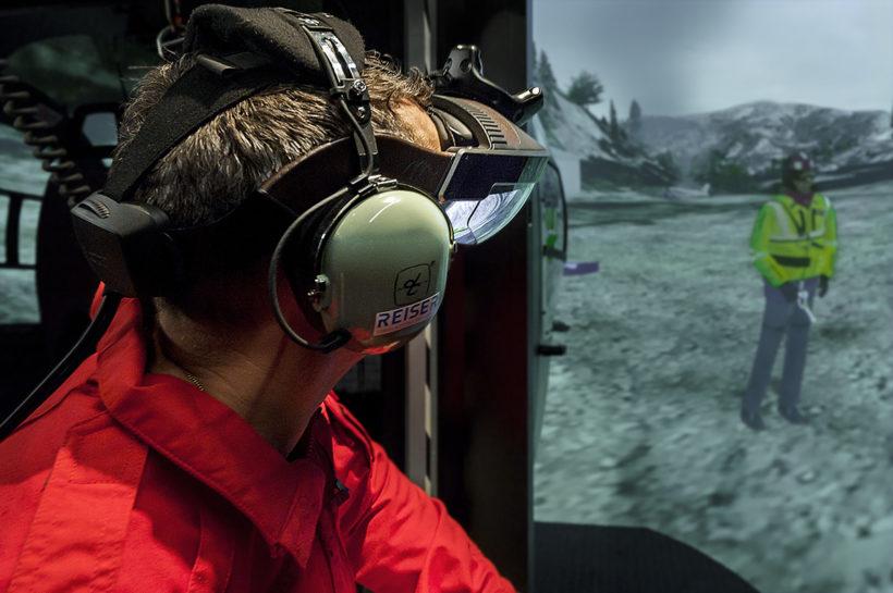 Mann mit Ohrschutz und VR-Brille schaut aus Flugzeug-Simulation