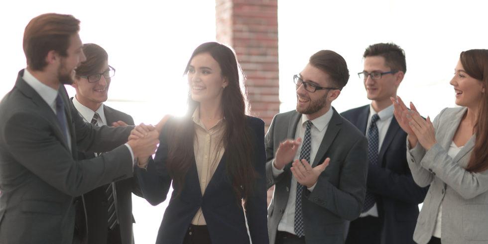 Kollegen stehen im Halbkreis und klatschen, Frau in der Mitte verabschiedet sich mit Handschlag