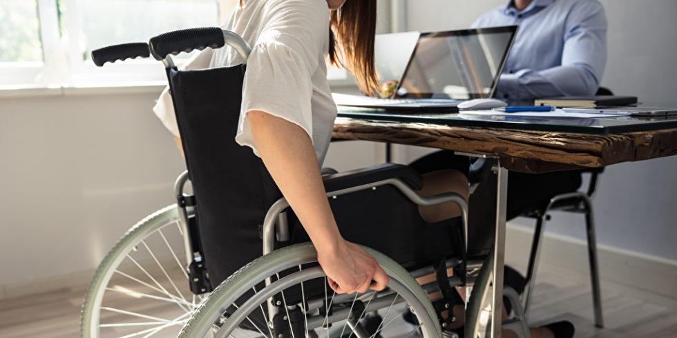 Frau mit steht mit Rollstuhl an einem Schreibtisch