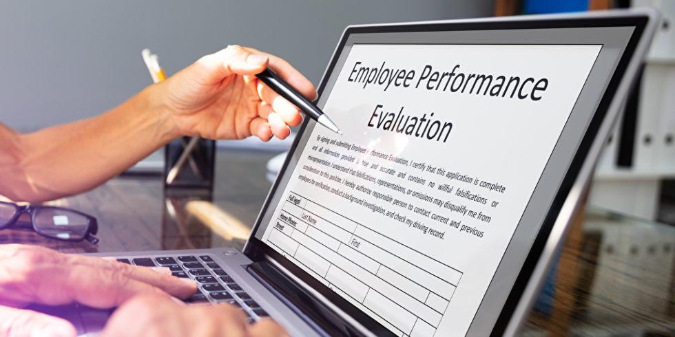 Laptop mit geöffnetem Dokument zur Beurteilung von Mitarbeiterleistungen