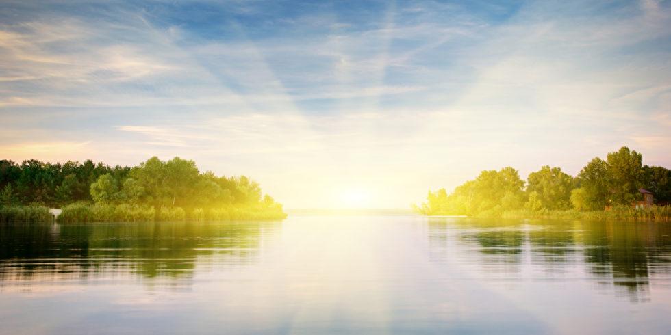 Fluss vor Landschaft mit Sonnenschein