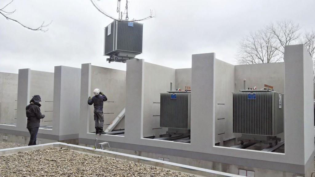 Die acht Transformatoren für das Kombikraftwerk werden angeliefert und montiert.Bild: AÜW