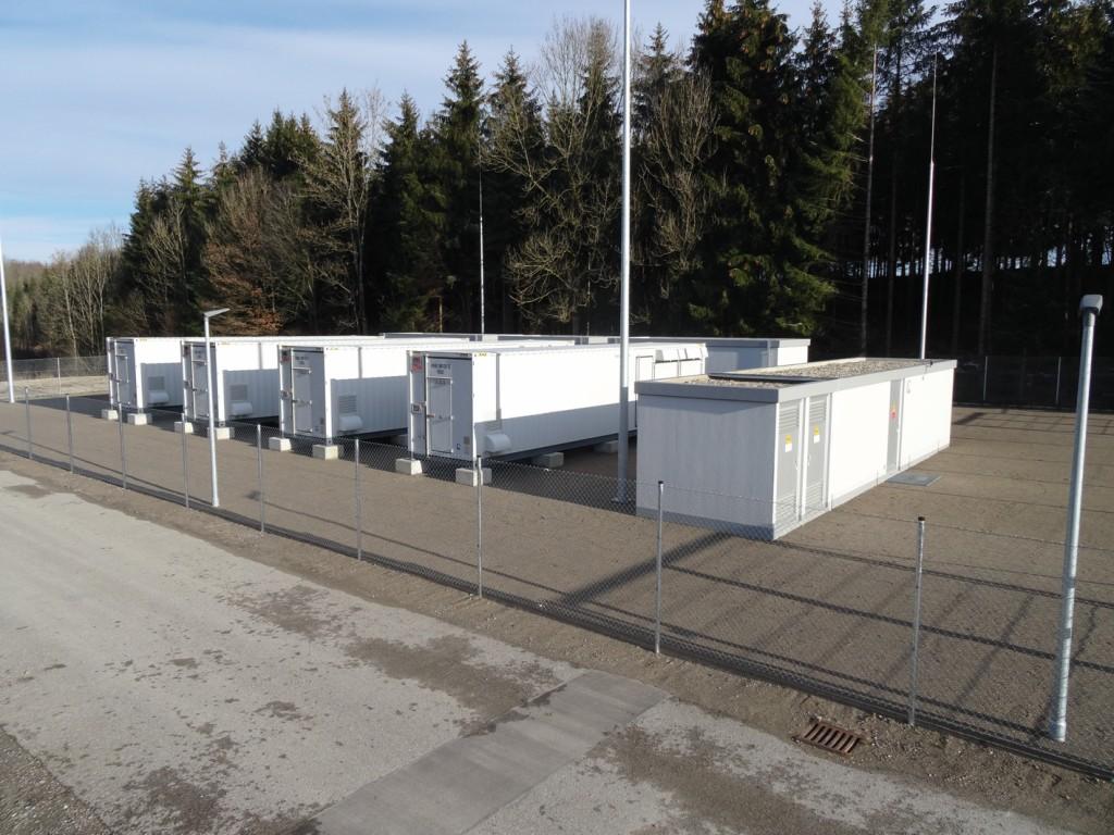 Auf einem Platz der AÜW bei Sulzberg stehen nebeneinander vier Container mit Batteriespeichern. Direkt davor steht die Mittelspannungsstation. Bild: AÜW