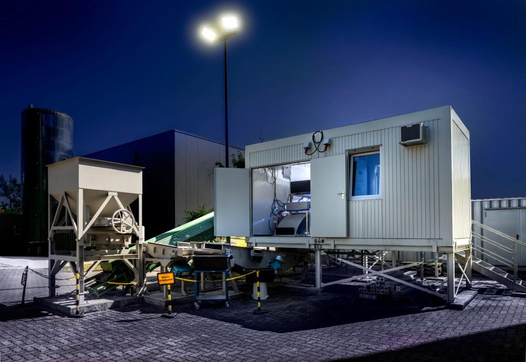 Links vor dem Container steht eine Brechanlage. Der zerkleinerte Bauschutt wird auf einem Förderband ins Innere des Containers transportiert, wo dieser mit einem Spektrometer untersucht wird.Bild: Fraunhofer IOSB