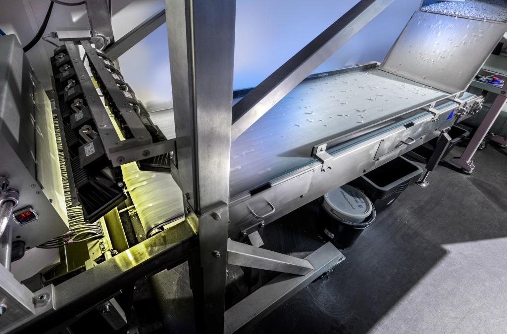 Einzelne Bauschutteile fallen im Container auf ein Laufband. Die Teile werden von einem Spektrometer erfasst. Bild: Fraunhofer IOSB