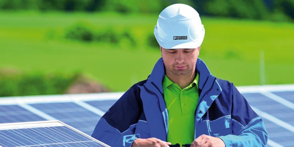 Mann mit Helm an Solaranlage