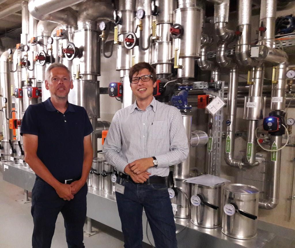 Ziehen eine positive Bilanz: André Pollex (l.) und Jörg Hüning vom Gebäudemanagement der Netz Lübeck GmbH, vor der Fernwärmeübergabestation. Bild: Stricker-Berghoff