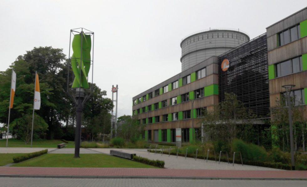"""Von außen ein grünes Gebäude mit Windkraftanlage und auch im """"Herzen"""" grün. Bild: Stricker-Berghoff"""