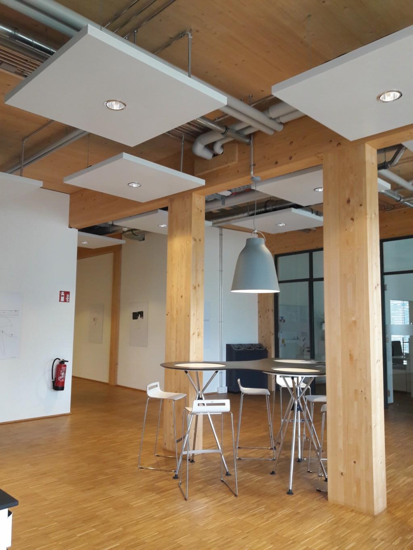 Blick zu den Schreibtischen in einem Flur mit Kommunikationsinsel und Glaswänden. Bild: Stricker-Berghoff