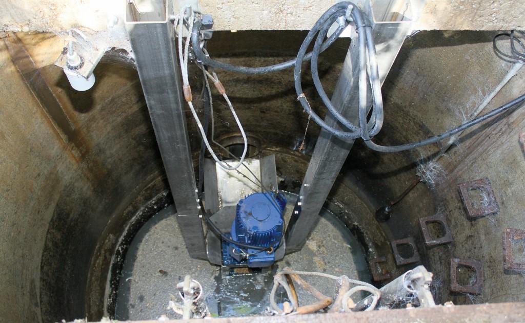 """Das """"Muffin-Monster"""" von Sulzer ist an der Schachtdecke hängend montiert. Der blaue Motor ist sichtbar. Der Zulauf erfolgt über einen offenen Kanal (links). Der Zerkleinerer arbeitet untertags alle 14 Minuten und zwischen 22 und 5 Uhr alle 40 Minuten jeweils 1 Minute. Bild: Sulzer"""