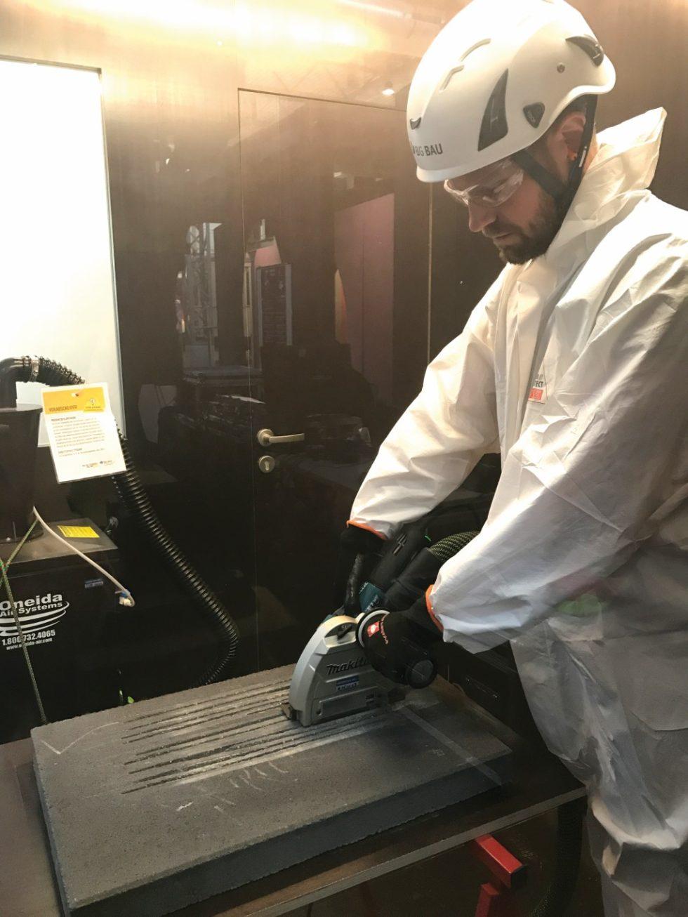 """Wird Staub beim Bearbeiten einer Betonplatte mit einem Trennschleifer direkt abgesagt, genügt eine Schutzbrille. Dies zeigte die BG Bau auf der Veranstaltung """"Aktionsprogramm gegen Staub in der Bauwirtschaft"""" im Juni 2019 in der Arbeitswelt Ausstellung der DASA in Dortmund. Bild: BG Bau"""