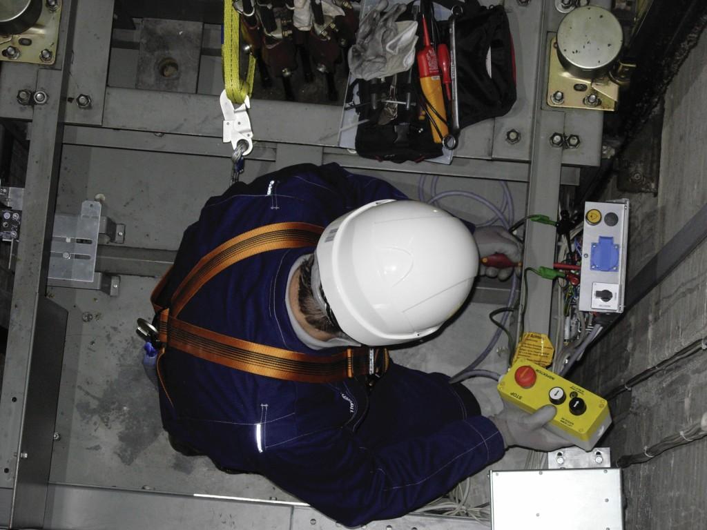 Bild 1 Das auf dem Fahrkorbdach vorhandene Geländer ist als alleinige Schutzmaßnahme gegen Absturz nicht ausreichend. Quelle: BGHM