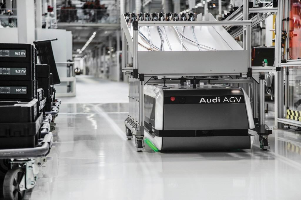 """Audi AGV: Using intelligent navigation software developed by Audi, the """"Audi AGV"""" (Automated Guided Vehicle) has the ability to supply goods from the warehouse to the assembly line totally independently and autonomously. Utilization of the FTS – driverless transport system – saves each factory employee up to 3.5 kilometers of walking per day. The FTS is equipped with a variety of sensors that allows it to recognize and maneuver around humans, factory equipment and other potential hindrances in the production facility."""
