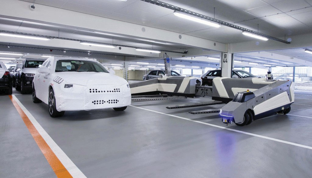 """In a pilot phase at the Audi plant in Ingolstadt that started in February, two robots independently transport cars from production to an interim storage area. From there, these driverless transport systems with the name """"Ray"""" later place the sorted Audi models into position according to their shipping destinations, so that logistics employees can load them onto railway wagons."""