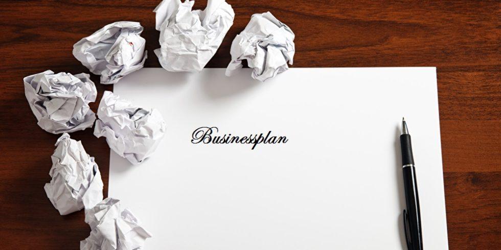 Businessplan steht auf einem weißen Blatt Papier, drum herum auf dem Tisch liegen zerknüllte Blätter