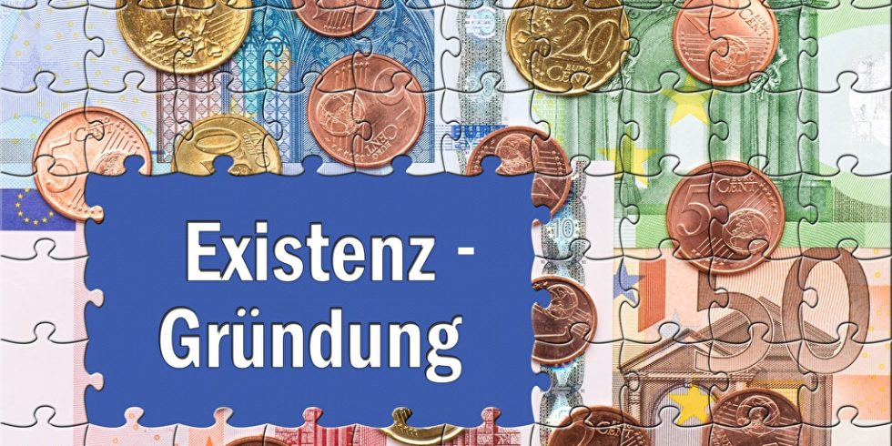 Kosten für die Selbstständigkeit veranschaulicht durch den Schriftzug Existenz-Gründung auf einem Puzzle aus Geld