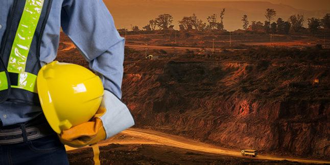 Ingenieur mit einem gelben Helm für die Sicherheit der Arbeiter auf dem Hintergrund der Kohlebergbau-Lkw fahren auf der Straße. Der Sonnenuntergang