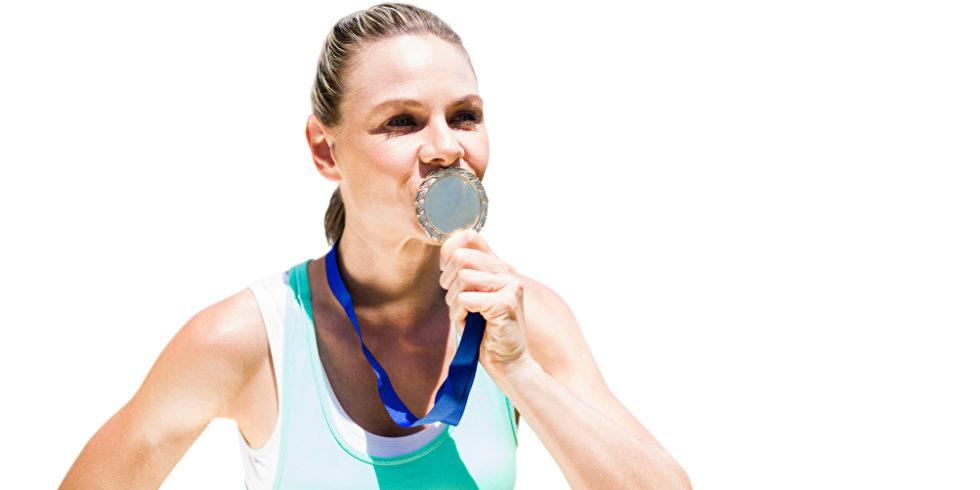 Sportlerin küsst Medaille