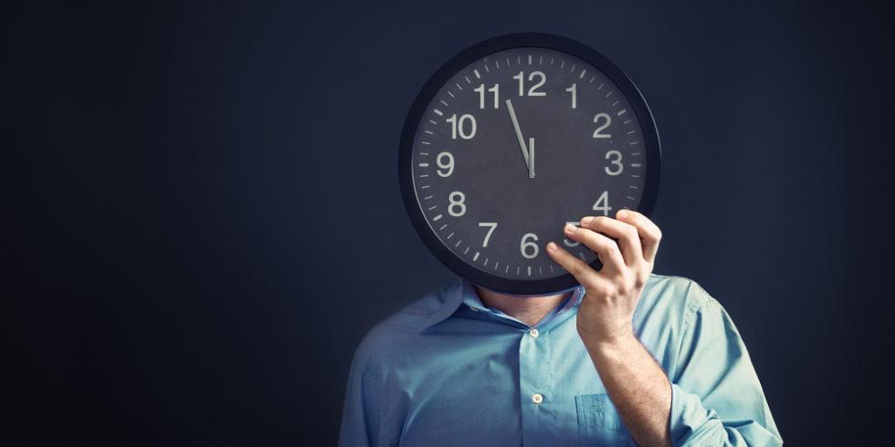 Uhr vor Gesicht eines Mannes